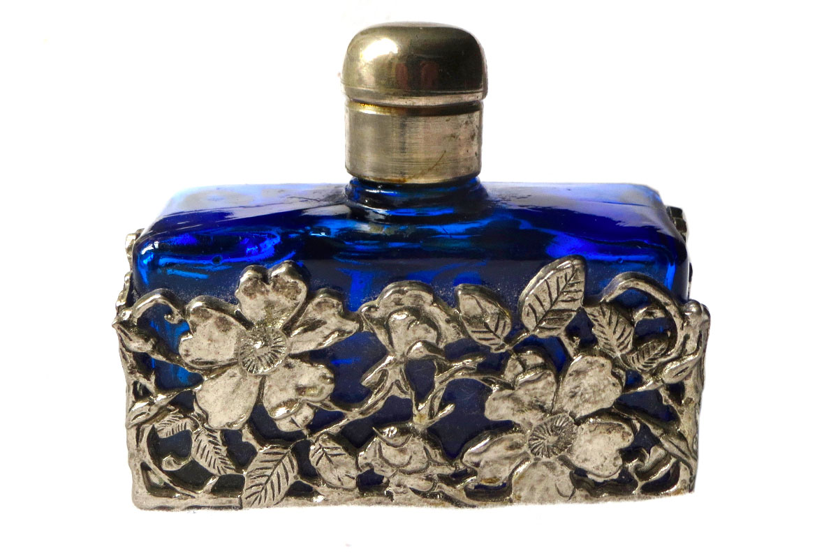 Glass Perfume Bottle – Cobalt Blue in White Metal Sleeve from Vee's Collectable, Antique & Vintage Emporium. Adding cobalt to glass gives it a distinctive blue tint and is highly collectible.