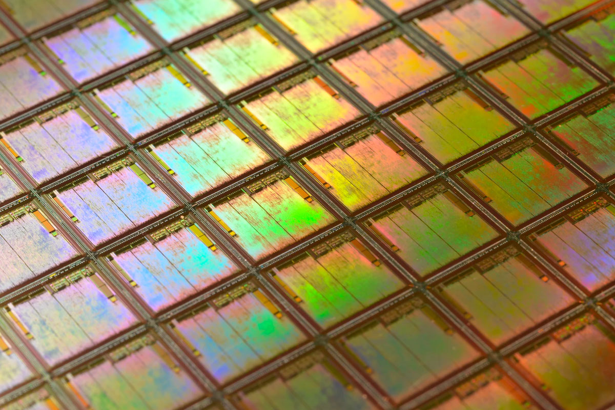 Close-up shot of a silicon wafer. Each square is a chip with microscopic transistors and circuits which goes into the processors that power our phones and computers.